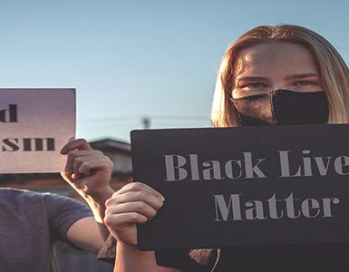 White woman holding BLM sign