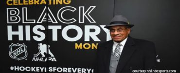 Willie O'Ree infront of Celebrating Black History Month Bbanner